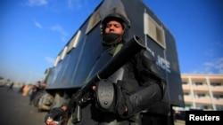 Një pjesëtar i policisë speciale të Egjiptit ruan para ndërtesës ku po zhvillohet procesi kundër Muhammad Morsit