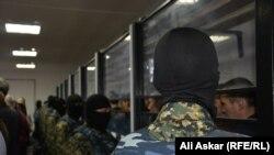Сотрудники спецназа стоят напротив обвиняемых по делу о вооруженных нападениях 5 июня. Актобе, 28 ноября 2016 года.