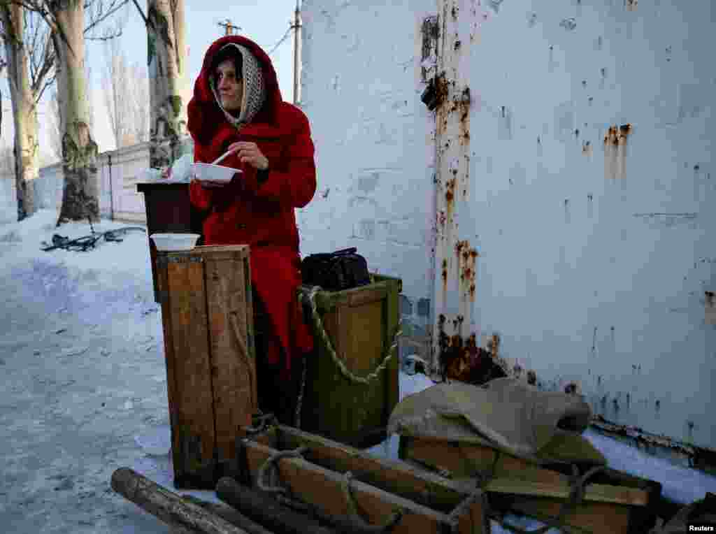 A local resident eats a meal at an emergency center after shelling hit supply infrastructure in the government-held industrial town of Avdiyivka, Ukraine, on February 1. (Reuters/Gleb Garanich)