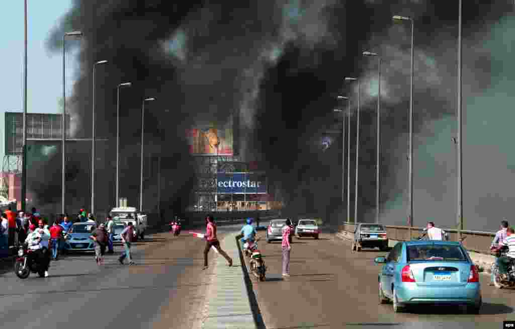 Egyptians flee the scene as others arrive on a bridge while smoke rises following clashes bertween opponents and supporters of ousted President Muhammad Morsi in Cairo. (epa/Ahmed Khaled)
