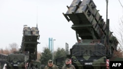 Soldiers of Germany's Air Defense Missile Squadron 2 walk past Patriot missile launchers in Bad Suelze.