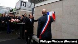 Франция президенті Франсуа Олланд (ортада) бір жыл бұрын болған теракт құрбандарына қойылған мемориалдық тақтайшаның ашылу рәсіміне қатысып тұр. Париж, 13 қараша 2016 жыл.