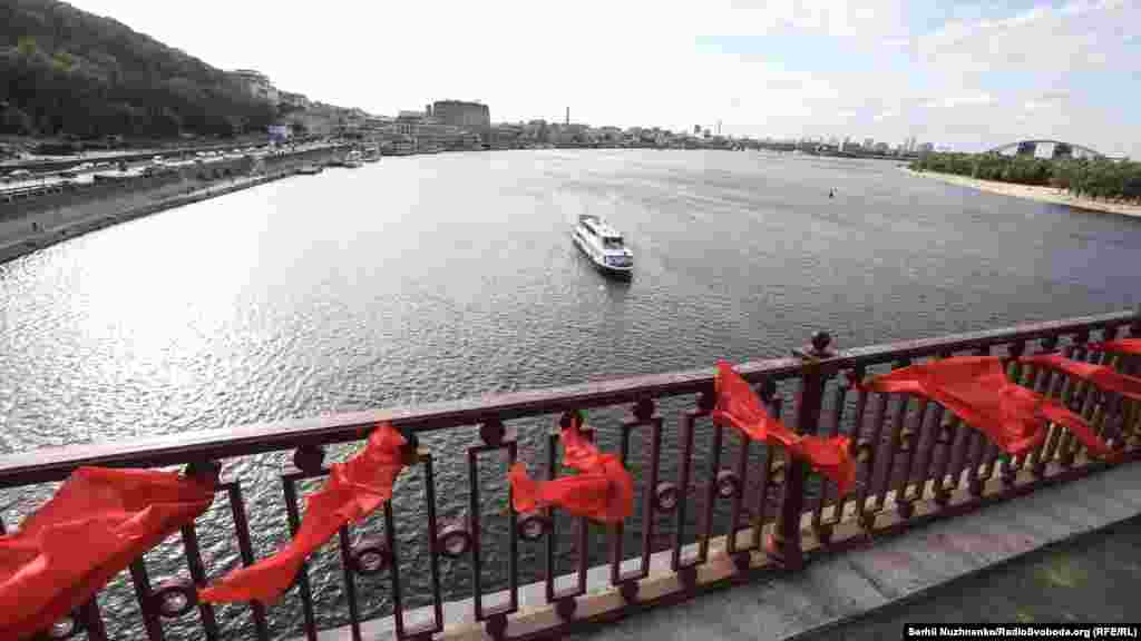 Вздовж опор мосту активісти розвісили 49 червоних полотен в пам'ять про загиблих