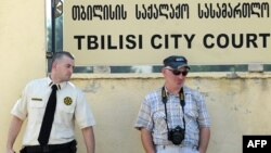 Тбилиси сотының алдында тұрған полицей мен фотограф. Көрнекі сурет