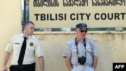 Полицейский смотрит на фотографа у здания городского суда Тбилиси, который в тот момент приговорил четырех журналистов к четырем годам тюрьмы по обвинению в шпионаже в пользу России. 22 июля 2011 года.