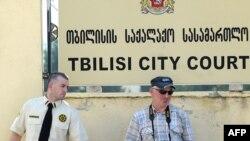 Тбилисидегі сот үйі алдында полиция қызметкері фотографқа қарап тұр. 22 шілде. 2011