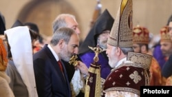 Armenia -- Prime Minister Nikol Pashinian kisses a cross held by Catholicos Garegin II during an Easter Mass at Yerevan's St. Gregory the Illuminator Cathedral, April 21, 2019.