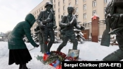 A woman places a red carnation near a picture of Russian pilot Roman Filipov, who was shot down in Syria, in front of the Russian Defense Ministry in Moscow on February 6.