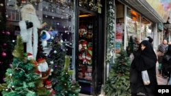 An Iranian chador clad woman passes by a Santa Claus shop in Tehran, December 22, 2014