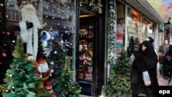 An Iranian chador clad woman passes by a Santa Claus shop in Tehran, December 22, 2014