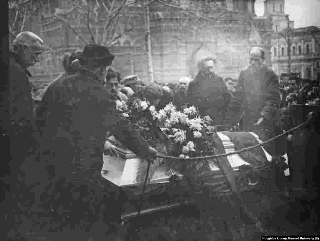 """Reed's coffin being interred at the base of the Kremlin walls  Reed's funeral was attended by revolutionaries Nikolai Bukharin and Aleksandra Kollontai, among others. """"There were speeches in English, French, German, and Russian. It took a very long time, and a mixture of rain and snow was falling,"""" a witness wrote. """"Although the poor widow [Bryant] fainted, her friends did not take her away. It was extremely painful to see this white-faced, unconscious woman lying back on the supporting arm of a Foreign Office official, more interested in the speeches than in the human agony."""""""