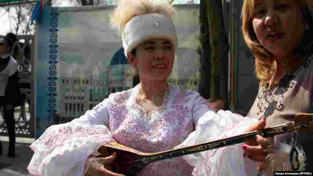 Қазақтың ұлттық костюмін киген әйел домбырамен ән шырқап тұр.