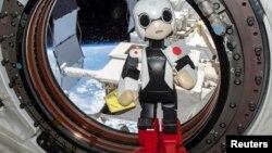 Робот Киробо с японским флагом в руке на борту Международной космической станции. 21 августа 2013 года.