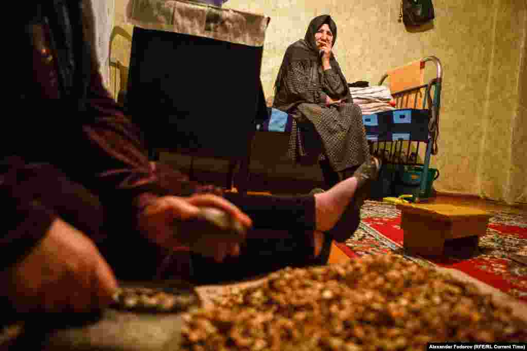 Musalmagomedova watches her daughter crushing apricot stones. Her daughter does not live here but comes to help as much as she can.