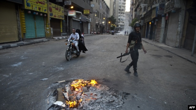 An Egyptian riot policeman takes position in downtown Cairo during clashes with supporters of Egypt's ousted Islamist president Mohammad Morsi on October 6.