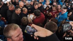 Russian President Vladimir Putin (center) is surrounded by admirers as he attends the Seliger youth camp on August 29.