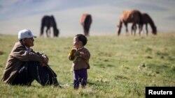 Фермер Тургынбай Еркинбеков с внуком на джайляу в 90 километрах от Алматы. 31 июля 2013 года. Иллюстративное фото.