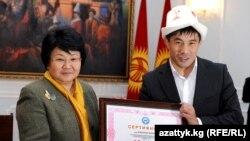 Президент Роза Отунбаева 16-Азия оюндарында алтын медалга татыган балбан Данияр Көбөновго сыйлык тапшырууда, 8-декабрь.