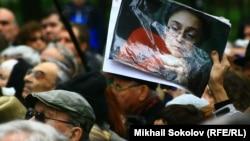 Участник мероприятия на седьмую годовщину убийства Политковской держит в руках ее портрет