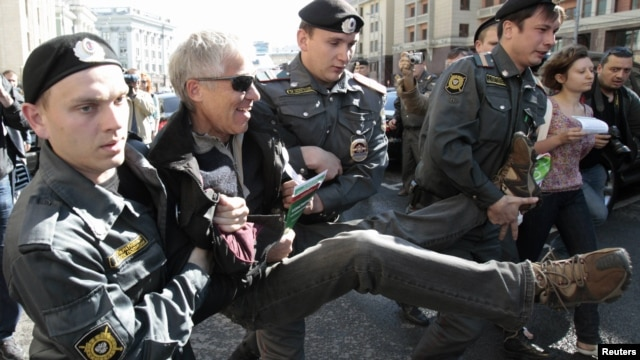 Russian police detain an opposition activist at a rally protesting a bill, initiated in the State Duma, to authorize bigger fines for a broader range of violations at demonstrations.