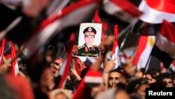 Противники президента Египта Мухаммеда Мурси с портретом министра обороны Абделя Фаттаха аль-Сиси на площади Тахрир в Каире, 3 июля 2013 года.