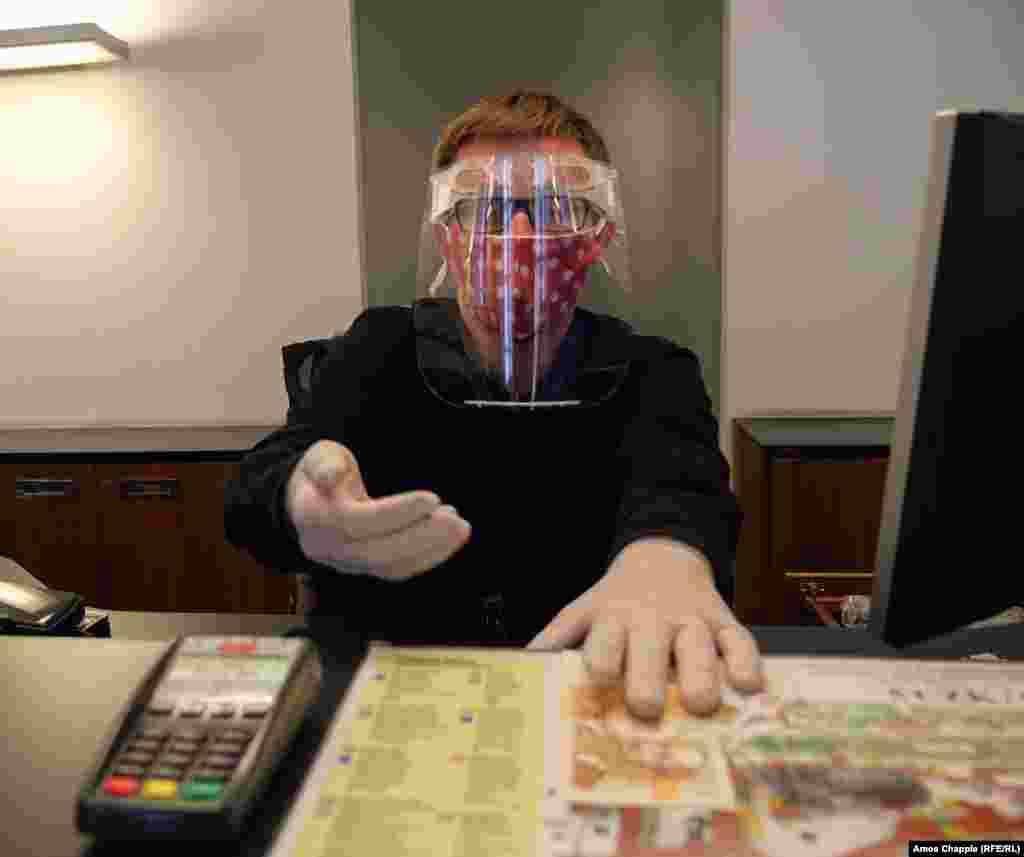Кассир в информационном центре Пражского града в маске и защитном экране