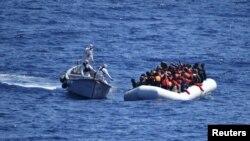 Migrantët qëndrojnë në anijen e tyre të gomës derisa u afrohet ekipi i shpëtimit i Marinës së Italisë