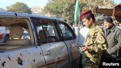 رجل أمن عراقي يتفحص سيارة متضررة من تفجير وقع في منطقة الكرادة ببغداد