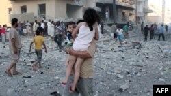 Սիրիա - Ռաքքա քաղաքում տղամարդը երեխաներին հեռացնում է այն վայրից, որտեղ հենց նոր պայթյուն է որոտացել, 7-ը օգոստոսի, 2013թ․