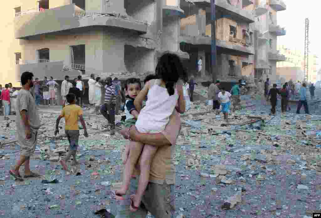 A man carries two children away from the scene of an explosion in the northern Syrian city of Raqqa. Three people were killed and dozens injured, including children. (AFP/Abdullah al-Sham)