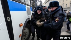 Police detain a protester during a rally near the Russian Defense Ministry headquarters in Moscow.