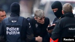 Belgian police take part in a search in the Brussels borough of Schaerbeek following deadly bombings in Brussels on March 22 that were claimed by Islamic State and killed at least 35 people.