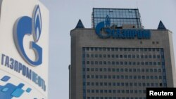 Russia -- A view shows a sign of a petrol station of Gazprom Neft company and the headquarters of the Russian natural gas producer Gazprom in Moscow, February 24, 2015