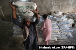 Laborers sort wheat flour sacks at a sale point in the southern seaport city of Karachi on January 20.