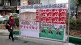 An Iranian woman walks past electoral posters on a street in Tehran.