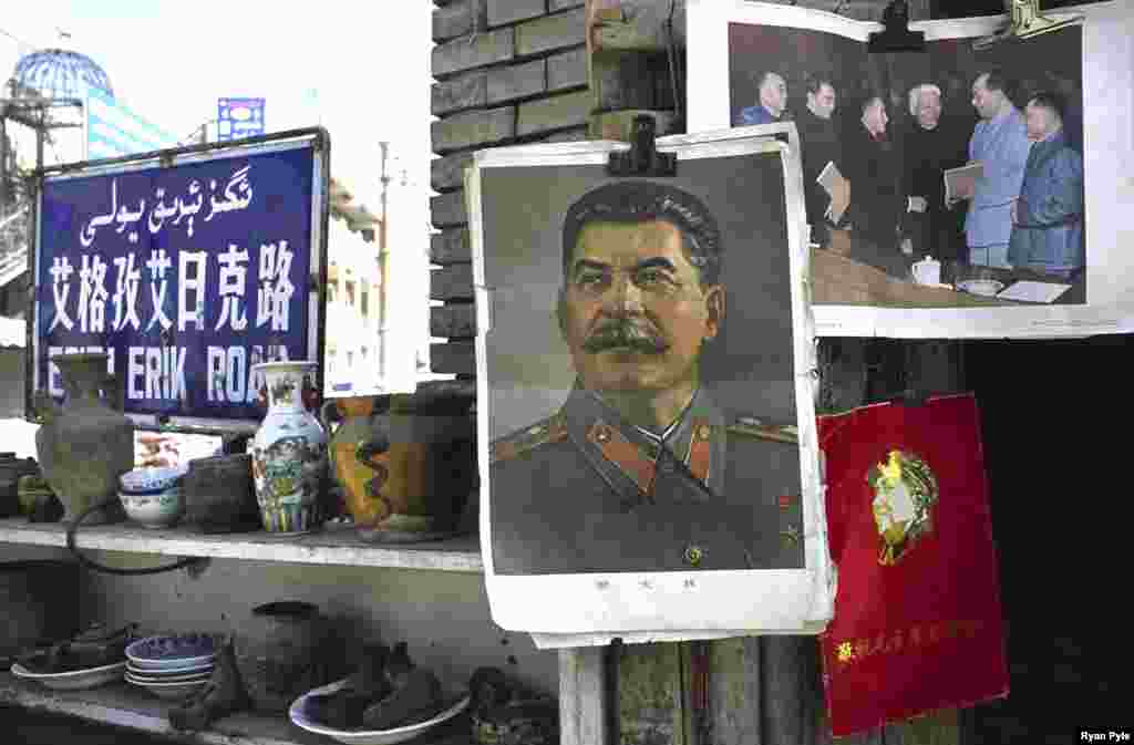 A picture of Soviet dictator Josef Stalin hangs beside one of Chairman Mao in a small street market. - Dominated by a gigantic statue of Mao, old Kashgar has seen many changes in recent decades, including the construction of a main street running through the old town center.
