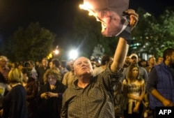 A protester burns a photo of Macedonia's president in Skopje on April 13.