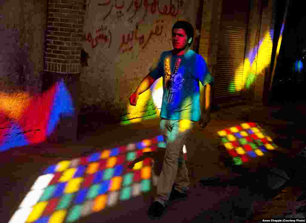 A young man walks by stained glass windows at the Tehran Bazaar. More than half of all Iranians are under the age of 30. Although the regime of Ayatollah Khomeini encouraged Iranians to produce large families, young Iranians are now seen as the biggest threat to the conservative Islamic regime.