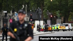 Armed police stand in the street after a car crashed outside the Houses of Parliament in Westminster, London, on August 14.