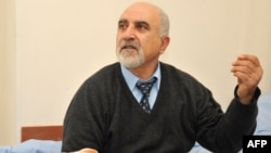 Presidential candidate Paruyr Hairikian speaks as he sits on his bed in a hospital room in Yerevan on February 5, less than a week after being shot in the right shoulder.