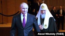 Vladimir Putin (solda) və Rusiya Patriarxı Kirill