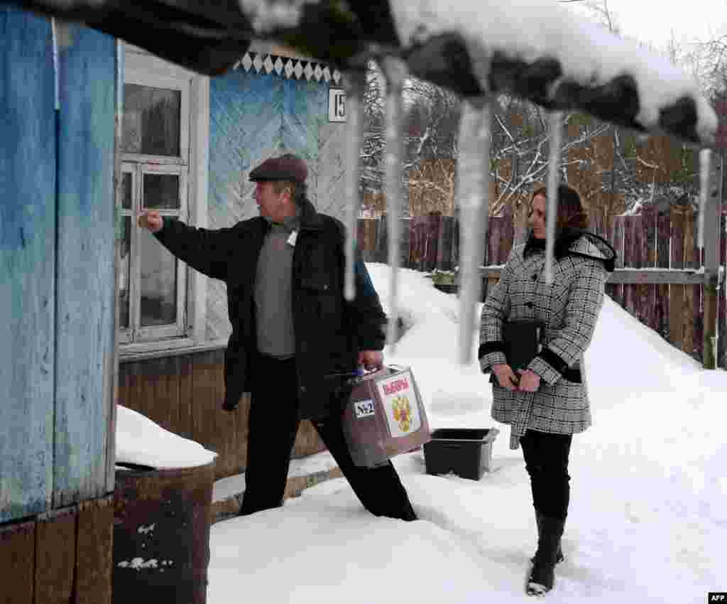 Members of a local electoral commission bring a mobile ballot to elderly people in their house in the village of Boreshino, some 40 km outside the western Russian city of Smolensk.