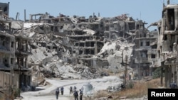 Workers collect the rubble of damaged buildings to be recycled and reused for reconstruction, under the supervision of UNDP) in the government-controlled district of Wadi al-Sayeh in Homs, Syria.