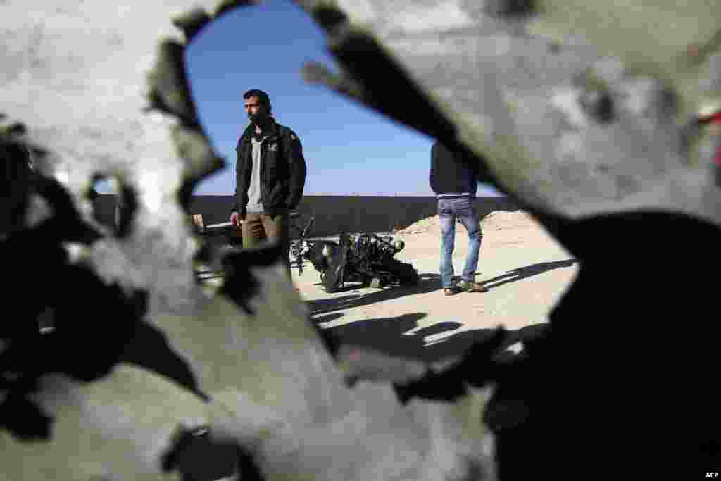 Palestinians walk past the wreckage of a motorbike whose driver was injured in an Israeli air strike on February 9 in Deir al-Balah, in the center of the Gaza Strip. (AFP/Said Khatib)