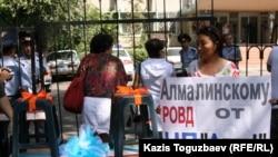 Айжан Әмірова Алмалы полиция басқармасына сыйлыққа әкелінген үстел-орындықтың жанында тұр. Алматы, 19 тамыз 2010 жыл.