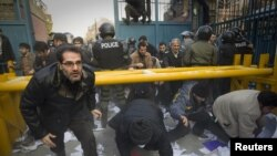 Protesters enter the gate of the British embassy in Tehran, as the police stand by. Nov. 29, 2011