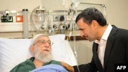A handout photo provided by the office of Iran's supreme leader Ayatollah Ali Khamenei shows former president Mahmoud Ahmadinejad (R) visiting him at a hospital in Tehran on September 8, 2014, after his prostate opertion.
