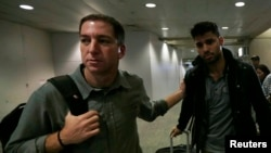 U.S. journalist Glenn Greenwald (left) walks with his partner David Miranda in Rio de Janeiro's International Airport on August 19.