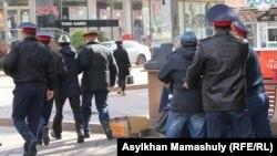 Адамдарды ұстап бара жатқан полиция қызметкерлері (Көрнекі сурет).