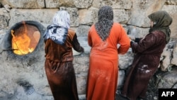 Сирійські жінки печуть хліб на вулиці
